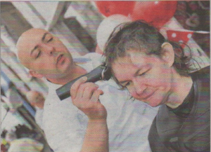 Shop manager Sue Smy having her head shaved for charity by Michael Monks from The Cube