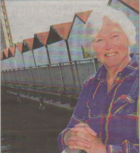 Trust chairman Doreen Stone with the huts behind